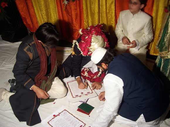 The groom can be seen signing a Nikah Nama or Islamic marriage contract